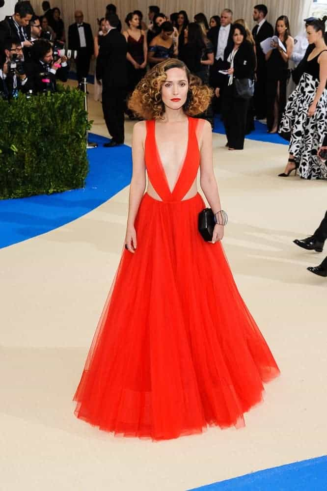 Rose Byrne attended the 2017 Metropolitan Museum of Art Costume Institute Gala at the Metropolitan Museum of Art in New York, NY on May 1, 2017. She was seen wearing a gorgeous orange gown paired with a shoulder-length curly hairstyle with highlights and layers.