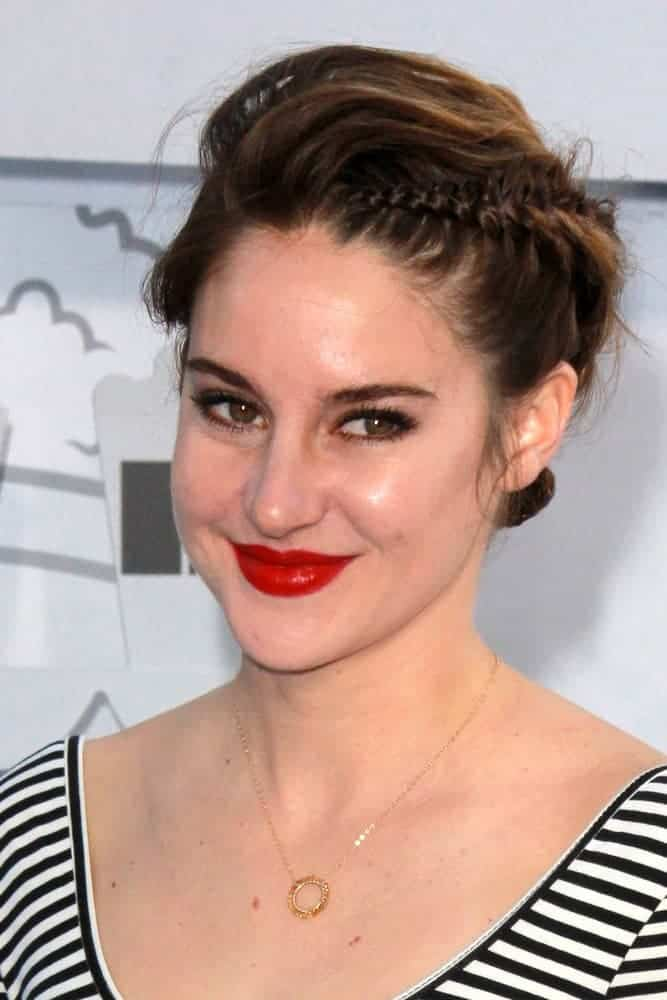 Shailene Woodley was at the MTV Movie Awards 2015 at the Nokia Theater on April 11, 2015, in Los Angeles, CA. She paired her red lips with a tousled brunette bun hairstyle with braids.
