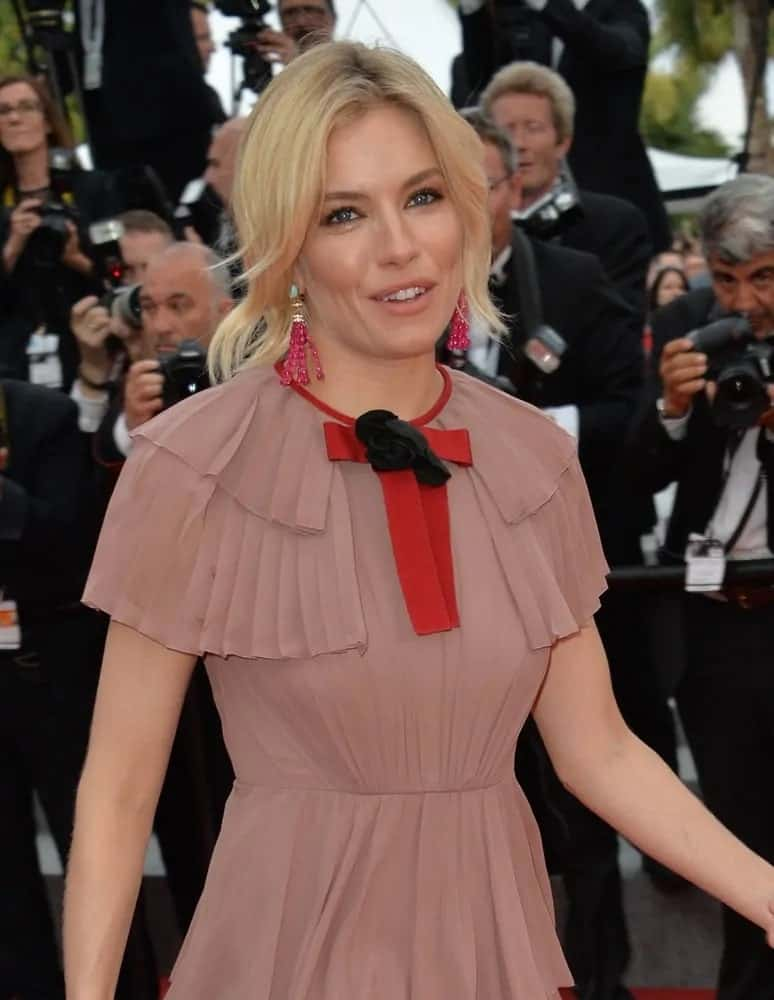 Sienna Miller exhibits a stunning aura in a flattering long, layered rose pink gown and finished her look in a messy center-part low bun hairstyle with a few strands framing her face as she attends the gala premiere for