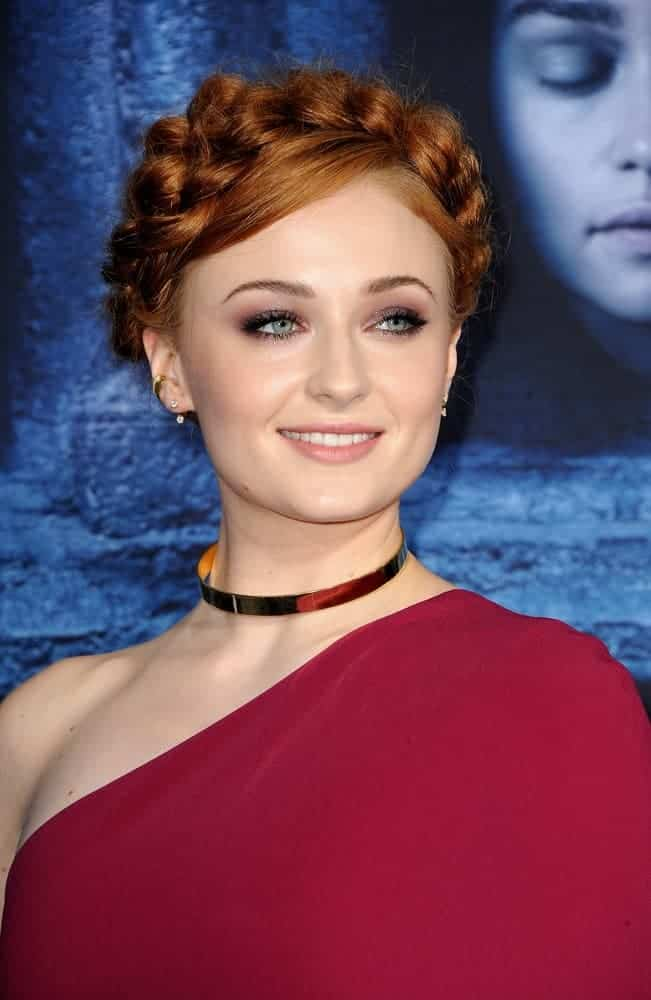 Sophie Turner attended the HBO's 'Game Of Thrones' season 6 premiere on April 10, 2016 wearing this princess-inspired plaited halo braid. She finished the gorgeous look with a one-shoulder red dress and a gold collar necklace.