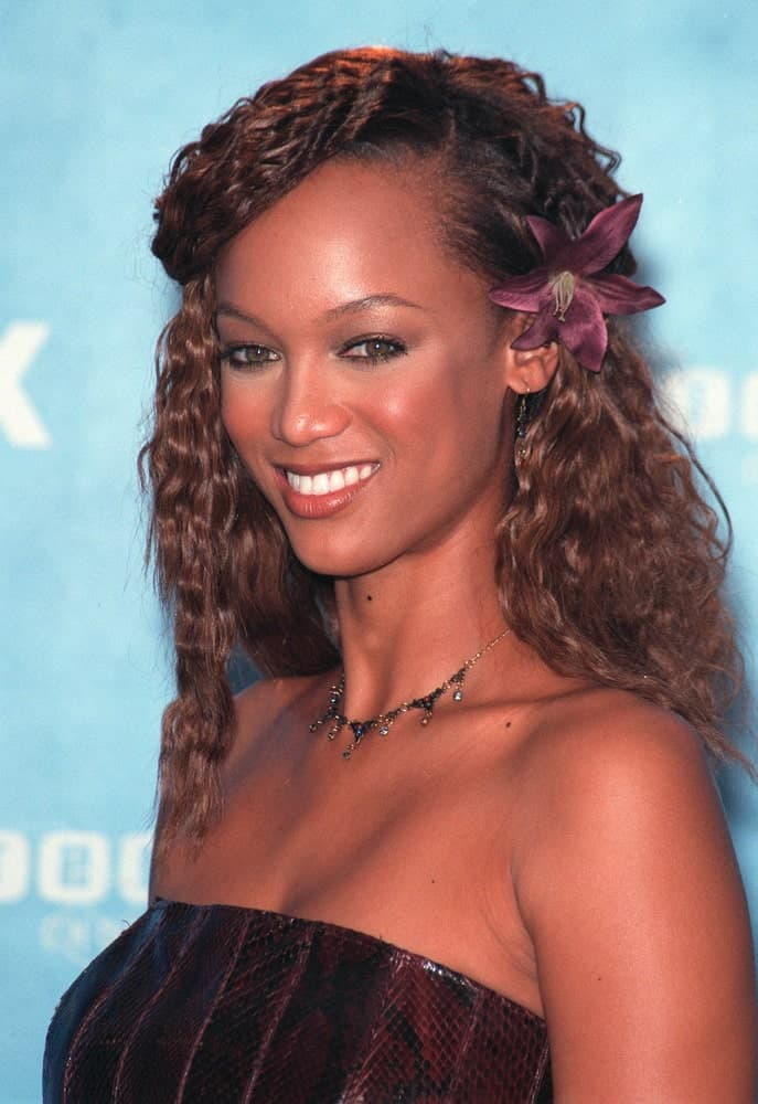 On August 1, 1999, supermodel Tyra Banks flashed her brilliant smile that complemented her long and curly side-swept hair decorated with a flower at the 1999 Teen Choice Awards in Santa Monica where she won for Teen Choice Model.