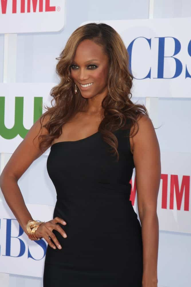 Tyra Banks's sexy black dress was complemented by her long and wavy side-swept hairstyle at the CBS, CW, and Showtime 2012 Summer TCA party at Beverly Hilton Hotel Adjacent Parking Lot on July 29, 2012 in Beverly Hills, CA.