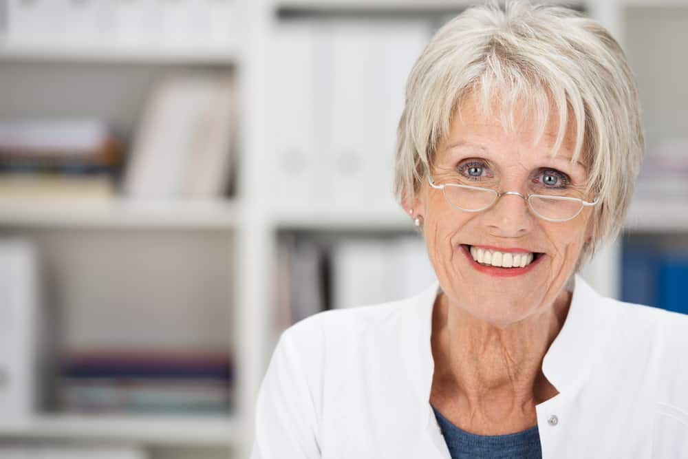 Woman with gray short haircut wearing glasses