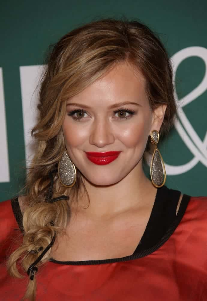 She's wearing an interesting fishtail side braid for with feathered bangs her blonde waves as she signs for 'Devoted' on October 14, 2011.