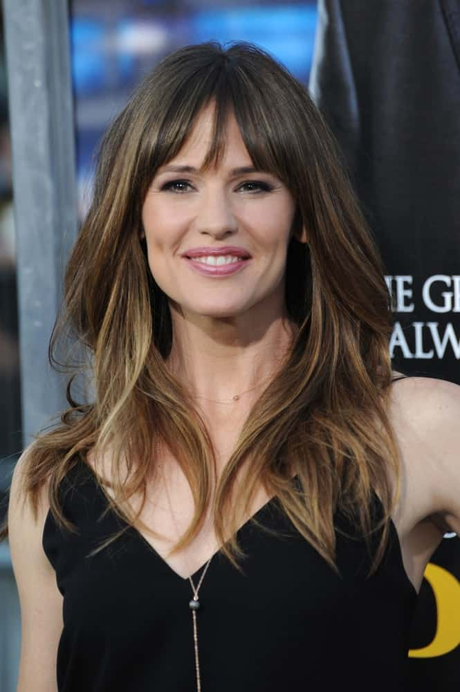 "The actress adds some volume and slight waves to her loose middle-parted mane with fringe bangs at the Los Angeles premiere of her movie ""Draft Day"" on April 7, 2014."