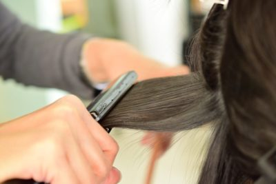 Woman getting hair straightened