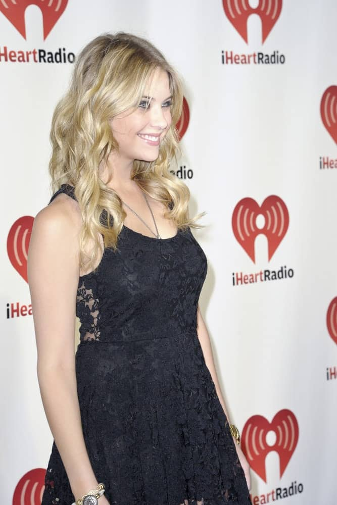Ashley Benson was at the 2011 iHeartRadio Music Festival on September 24, 2011 at the MGM Grand Garden Arena in Las Vegas, Nevada. She paired her stunning black floral dress with a loose and curly blonde hairstyle with a slight tousle and layers.