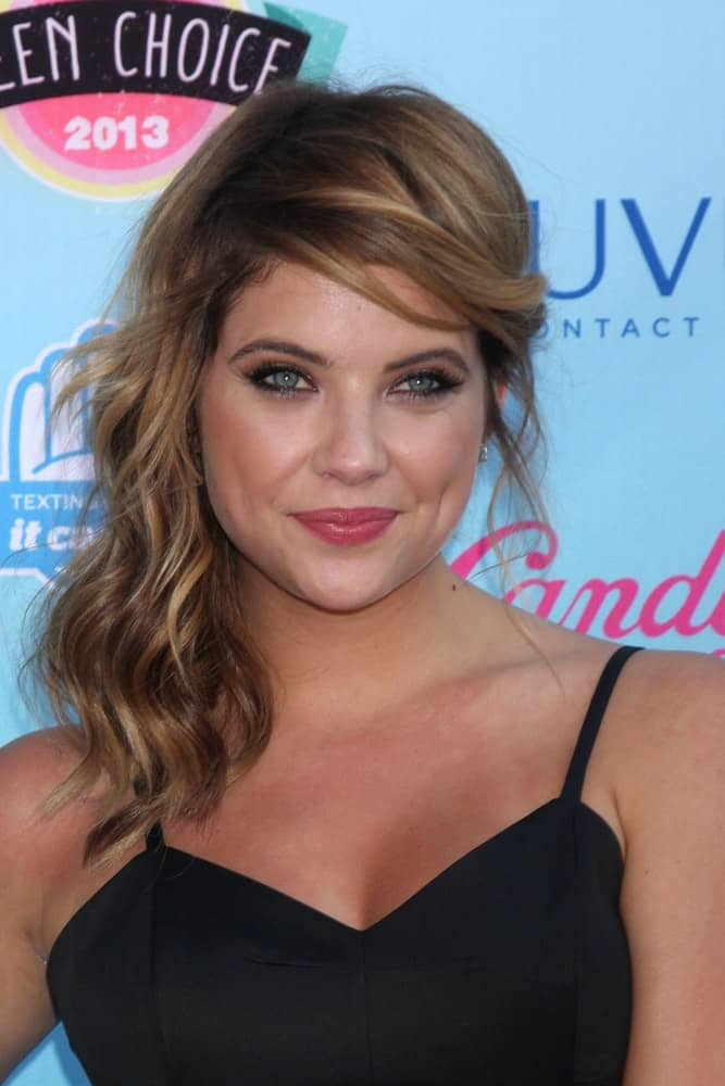Ashley Benson was at the 2013 Teen Choice Awards at the Gibson Ampitheater Universal on August 11, 2013 in Los Angeles, CA. She wore a stunning black dress with her highlighted side-swept hairstyle with beach waves and a brown tone.