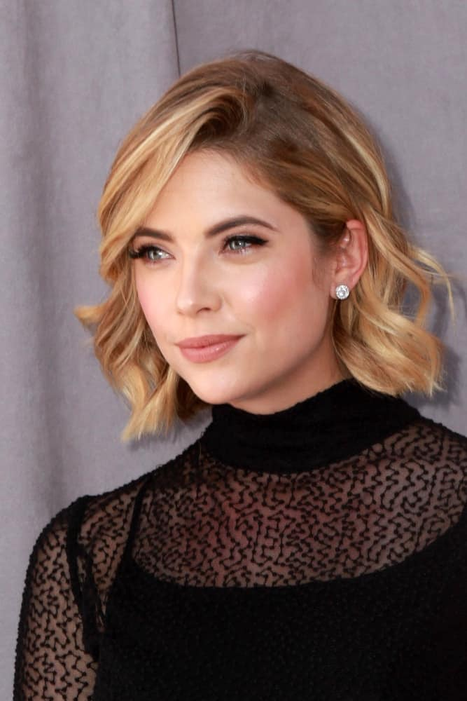 Ashley Benson was at the Comedy Central Roast of Justin Bieber at the Sony Pictures Studios on March 14, 2015 in Culver City, CA. She was lovely in a stunning all-black outfit with her chin-length curly sandy blonde hairstyle with long side-swept bangs.