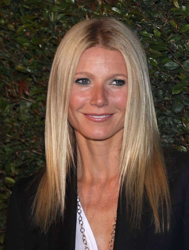 Gwyneth Paltrow looking sleek in her iconic fine blonde hair that's center-parted during the