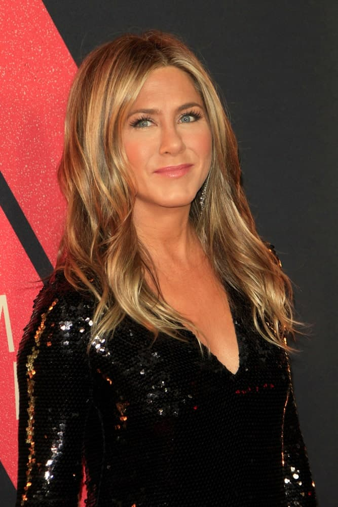 Jeniffer Aniston is shining in a black sequined dress along with her voluminous blonde waves that are highlighted and center-parted. This look was worn at the