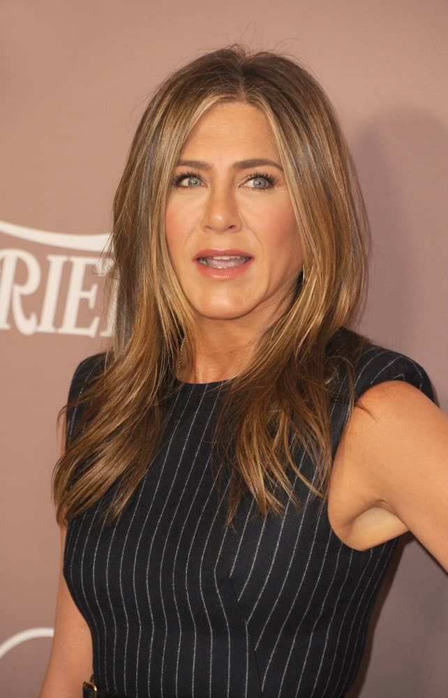 Jennifer Aniston with her signature hairstyle featuring her straight layered hair in highlighted blonde complemented with a black striped dress. This look was worn at the Variety's 2019 Power Of Women in Beverly Wilshire Four Seasons Hotel held on October 11, 2019.
