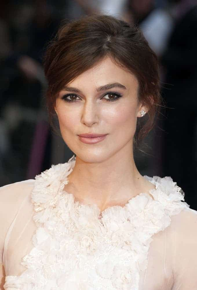 Keira Knightley attended the UK premiere of Anna Karenina at Odeon Leicester Square, London on May 9, 2012. She wore a lovely white dress with her messy side-swept bun hairstyle and simple makeup.