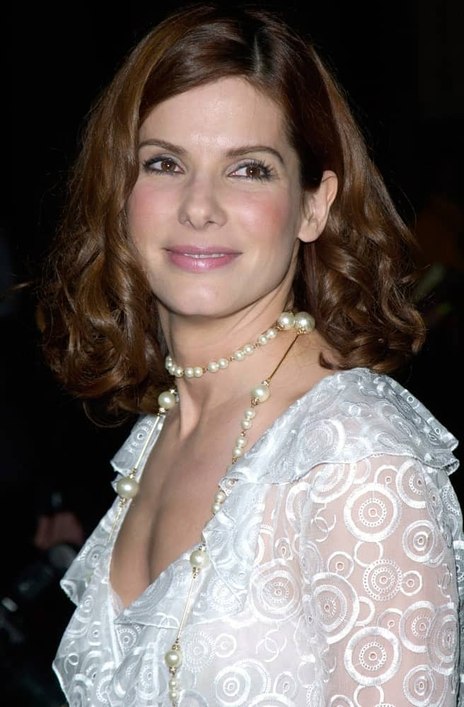 Last April 10, 2001, actress Sandra Bullock was at the 2001 Blockbuster Awards in Los Angeles. Her curly shoulder-length hairstyle complements her white sheer patterned outfit.