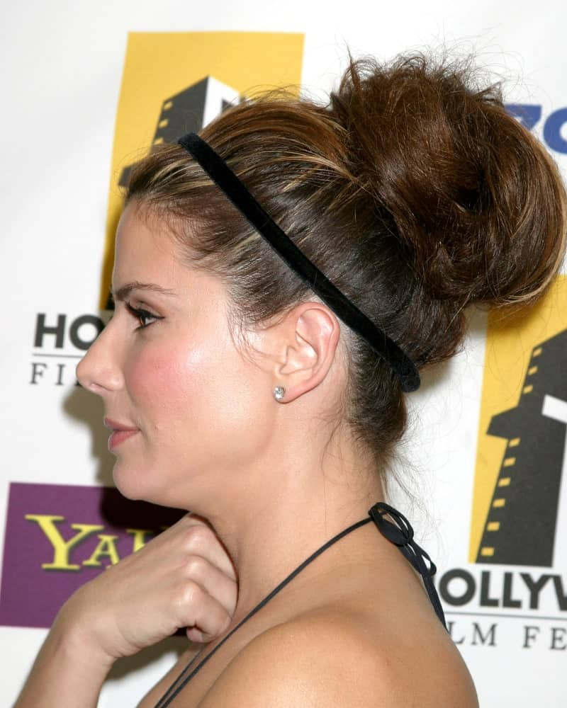 Sandra Bullock was at Hollywood Film Festival Gala in Beverly Hilton Hotel back in October 24, 2005. She had her thick brunette highlighted hair styled up into a large bun hairstyle supported by a hair band.