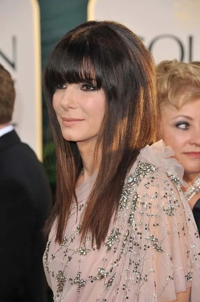 Sandra Bullock was at the 68th Annual Golden Globe Awards back in January 16, 2011. She wore a lovely sheer dress with her straight and layered hair complemented by blunt bangs.