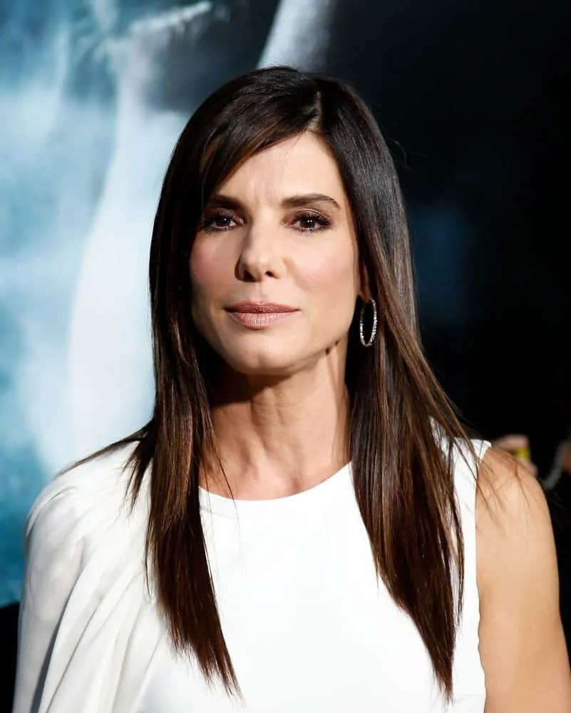 Sandra Bullock had long and straight layers with a side part hairstyle that complemented her white dress at the 'Gravity' premiere last October 1, 2013.