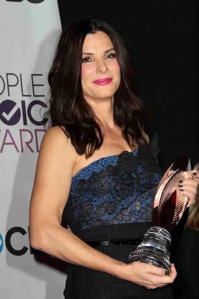 Sandra Bullock went with a carefree and gorgeous loose layered waves with a center part when she accepted her award at the 2013 People's Choice Awards Press Room back in January 9, 2013.