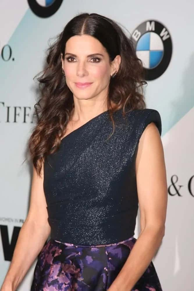 Sandra Bullock wore her hair slick and center-parted at the top and curly down the ends at the Women In Film 2015 Crystal + Lucy Awards back in June 16, 2015.