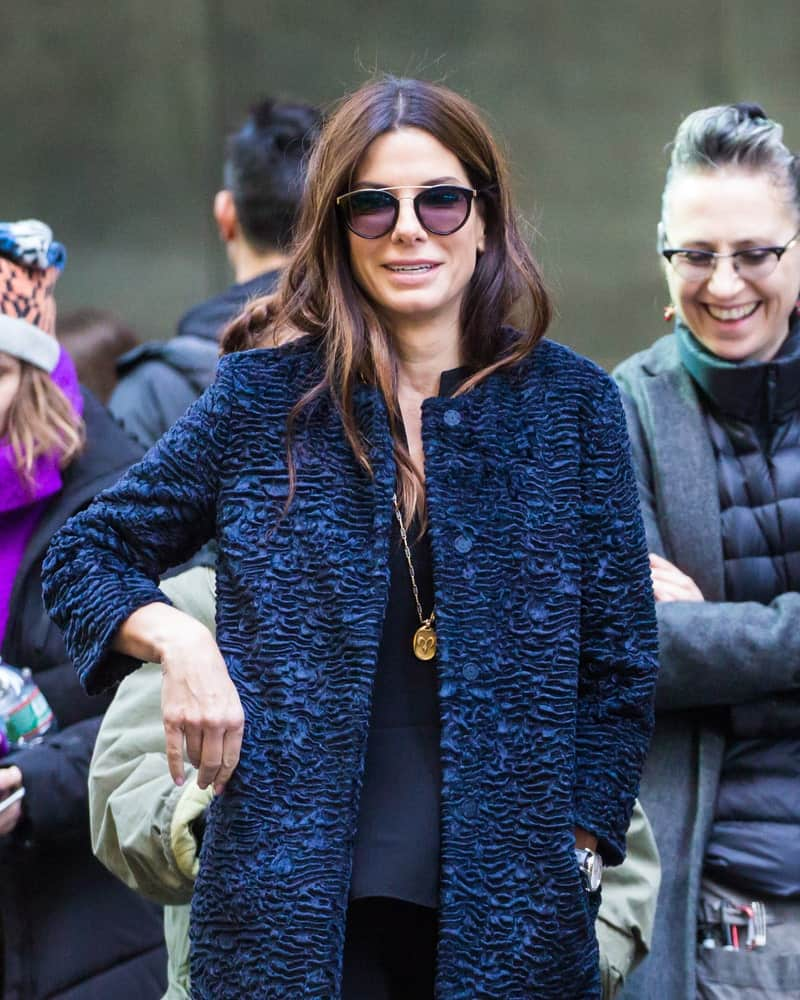 Sandra Bullock was seen on set of 'Ocean's 8' last October 28, 2016 in New York City. She wore a casual outfit that went great with her tousled and loose wavy hairstyle that has highlights.