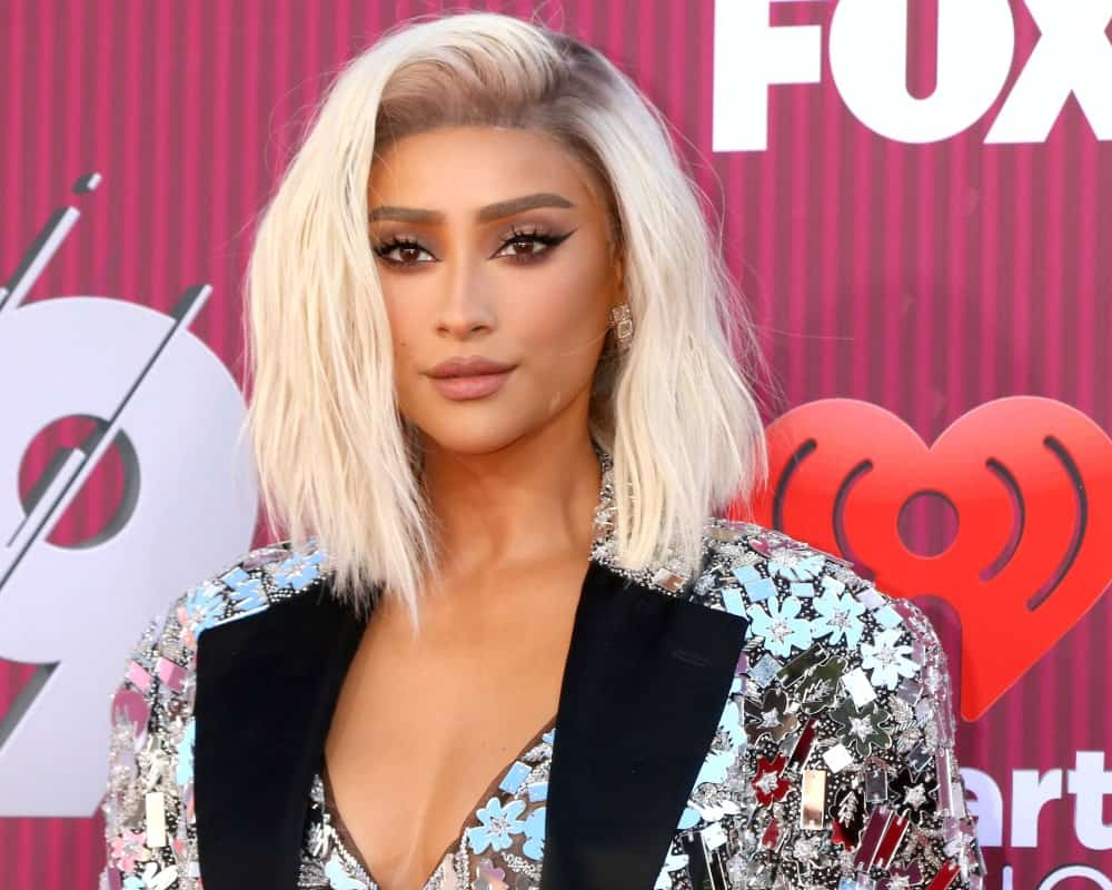 Shay Mitchell arrived at the iHeart Radio Music Awards on March 14, 2019, wearing her platinum blonde hair that's side-swept and tousled.