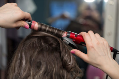 Woman getting hair curled with curling iron