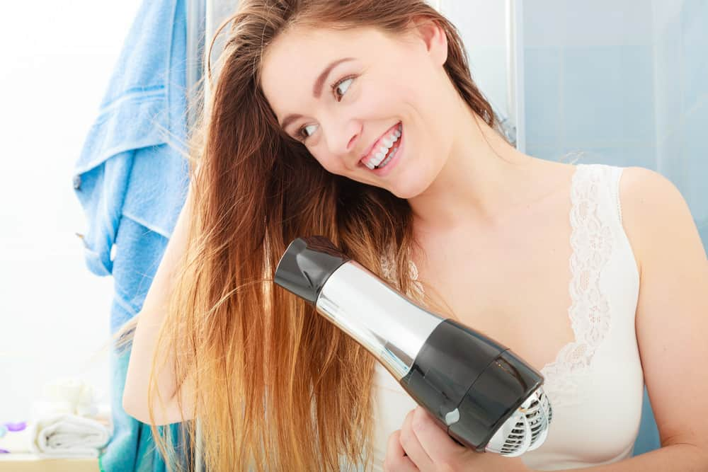 Young woman blow drying her hair