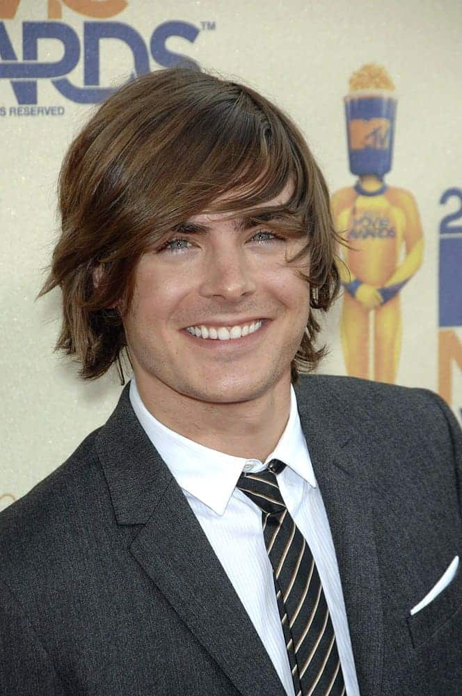 Zac Efron flashed a sweet smile with his long tousled locks styled with side-swept bangs at the 2009 MTV Movie Awards held on May 31, 2009. He wore a gray suit paired with a black striped tie.
