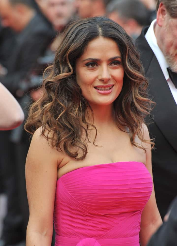 Salma Hayek flashed fresh beauty in tousled waves for her highlighted brunette mane during the gala premiere of
