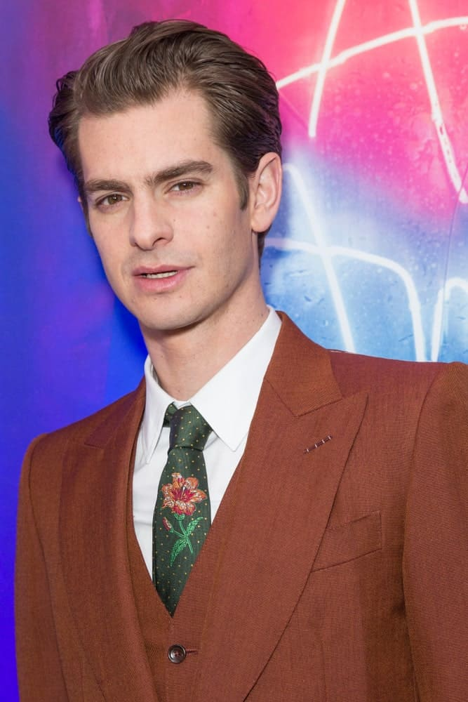Andrew Garfield is undeniably handsome with a comb over look at the revival of Angels in America play after party last March 25, 2018. It was completed with a brown suit that's paired with a lovely floral print tie.