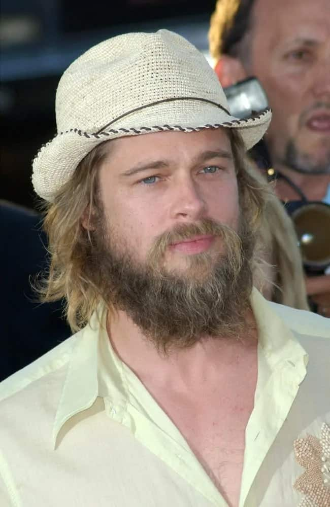 Brad Pitt wore a white fedora on top of his long and layered hair and massively unkempt bearded face back in 2002. He paired this with a casual white button down shirt.