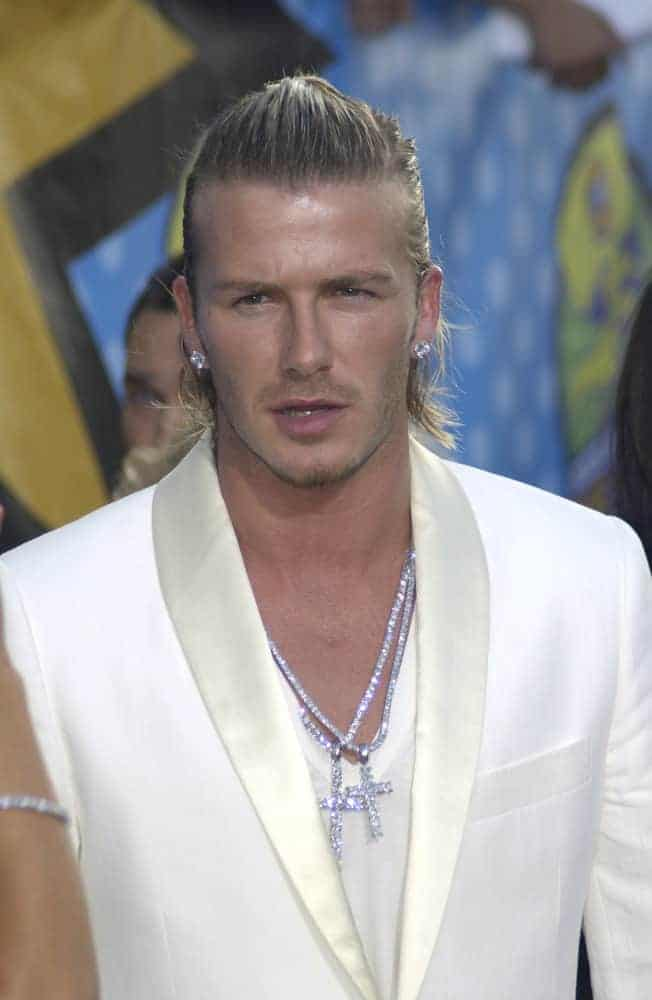 David Beckham looked fashionable with a top knot and white suit during the 2003 MTV Movie Awards on May 31st in Los Angeles. HE finished the look with sparkling blings and earrings.