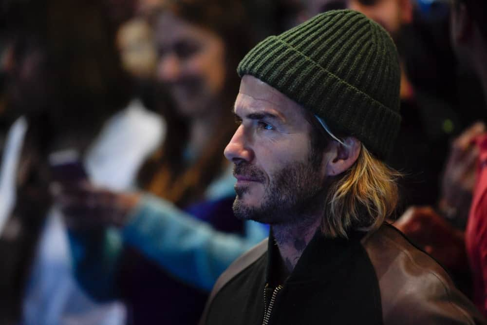 David Beckham paired his long blonde hair with a green beanie as he enjoys the final game between Grigor Dimitrov & David Goffin at Nitto ATP Finals World Tour on November 19, 2017.