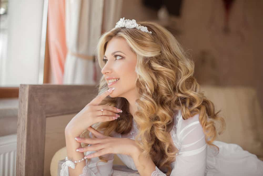 Down wedding hairstyle with blonde, wavy hair.