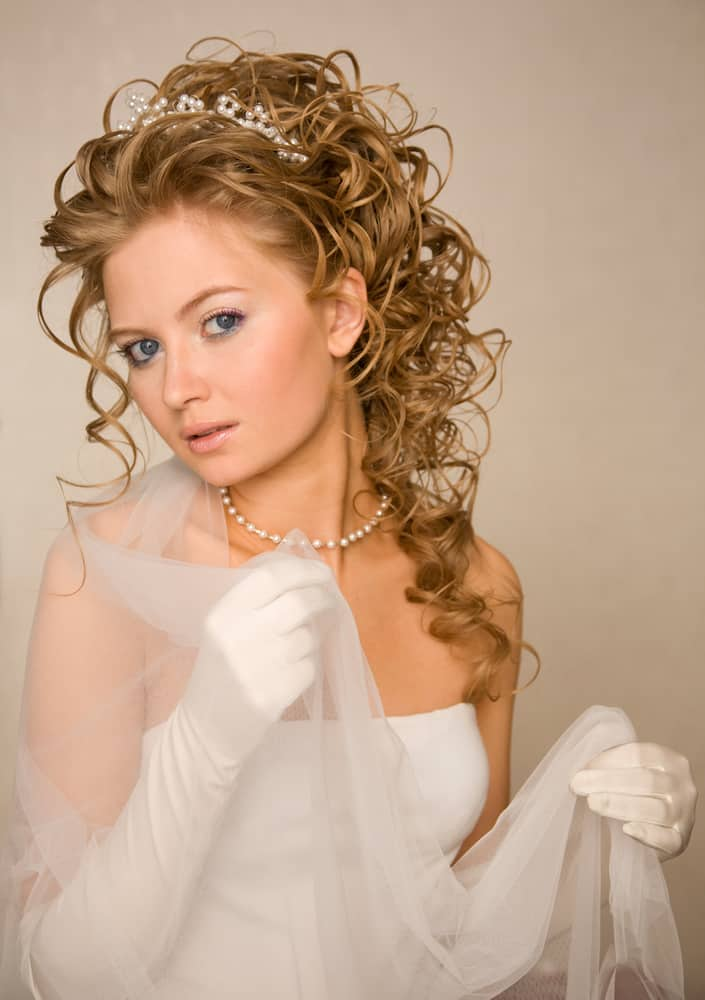 This long layered curly blonde locks with a pearl headband hairstyle will put a romantic twist in your wedding day.