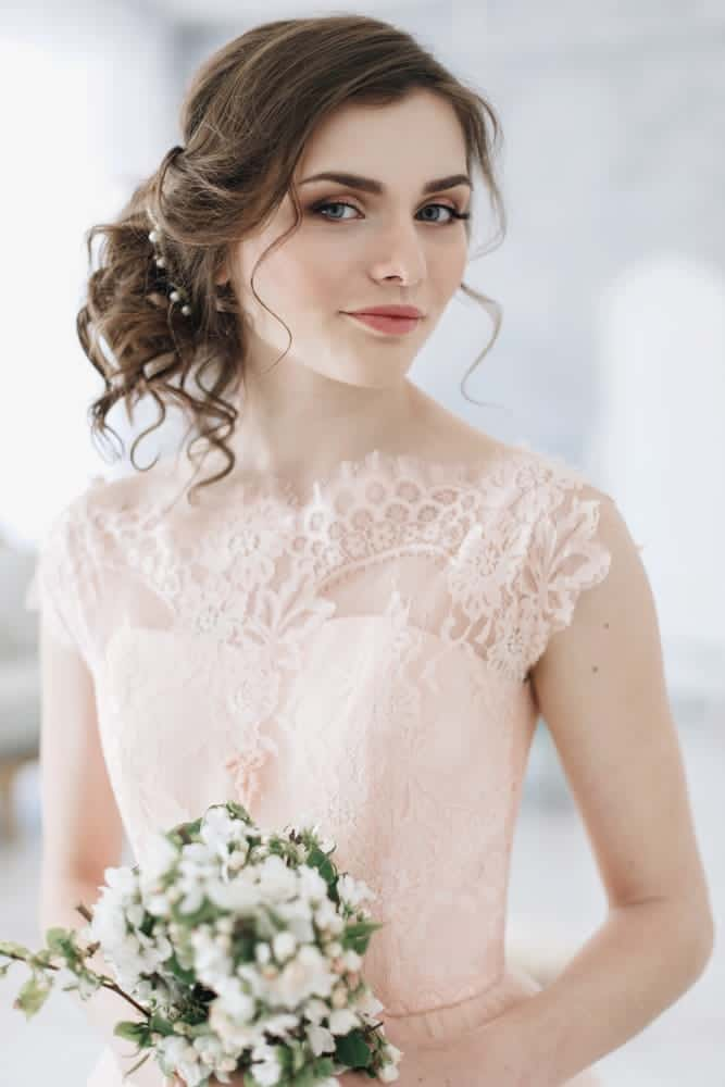 Here's a messy but chic side-swept bun with a few rogue pieces out around the face, a beautiful style you can rock with a wedding dress.