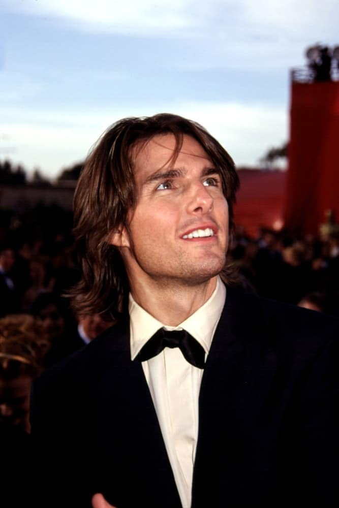 Tom Cruise wore a long and layered hairstyle that is parted in the middle paired with five o'clock shadow when he attended the Academy Awards back in 2000.