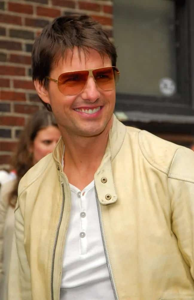 Tom Cruise wore a casual light tan jacket with his fringe bangs  and a pair of vintage sunglasses at