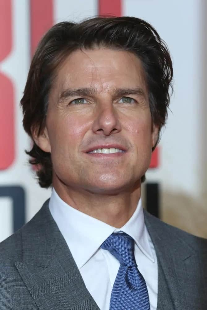 Tom Cruise wore a gray suit to pair with his long and shaggy hairstyle during the Mission Impossible: Rogue Nation - UK special screening at the BFI IMAX on Jul 25, 2015 in London.