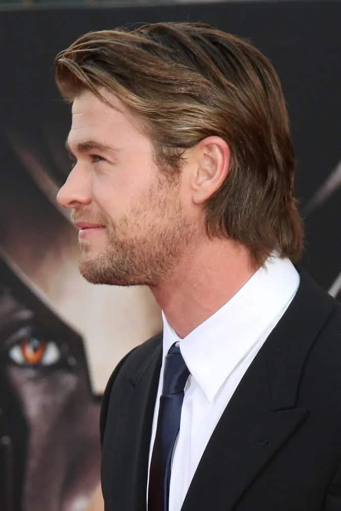 Chris Hemsworth paired his classic black suit and navy blue tie with a mid-length layered and highlighted side swept hairdo at the Empire Film Awards 2012.