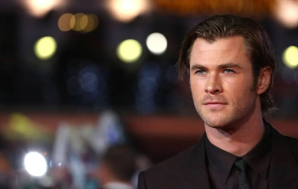 Chris Hemsworth had a mid-length slick side-swept hairstyle paired with a charcoal black suit during the world premiere of Thor The Dark World in London, 2013.