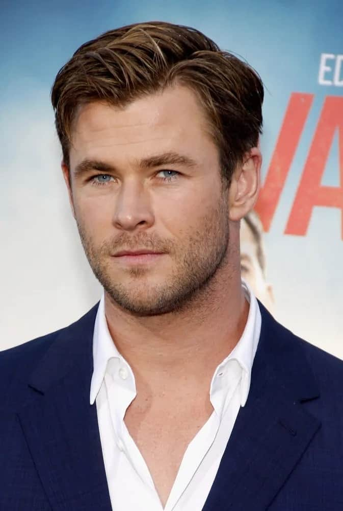 Chris Hemsworth wore his short side swept hairstyle with subtle highlights at the Los Angeles premiere of 'Vacation' in 2015. It matches well with his simple blue suit and white button shirt.