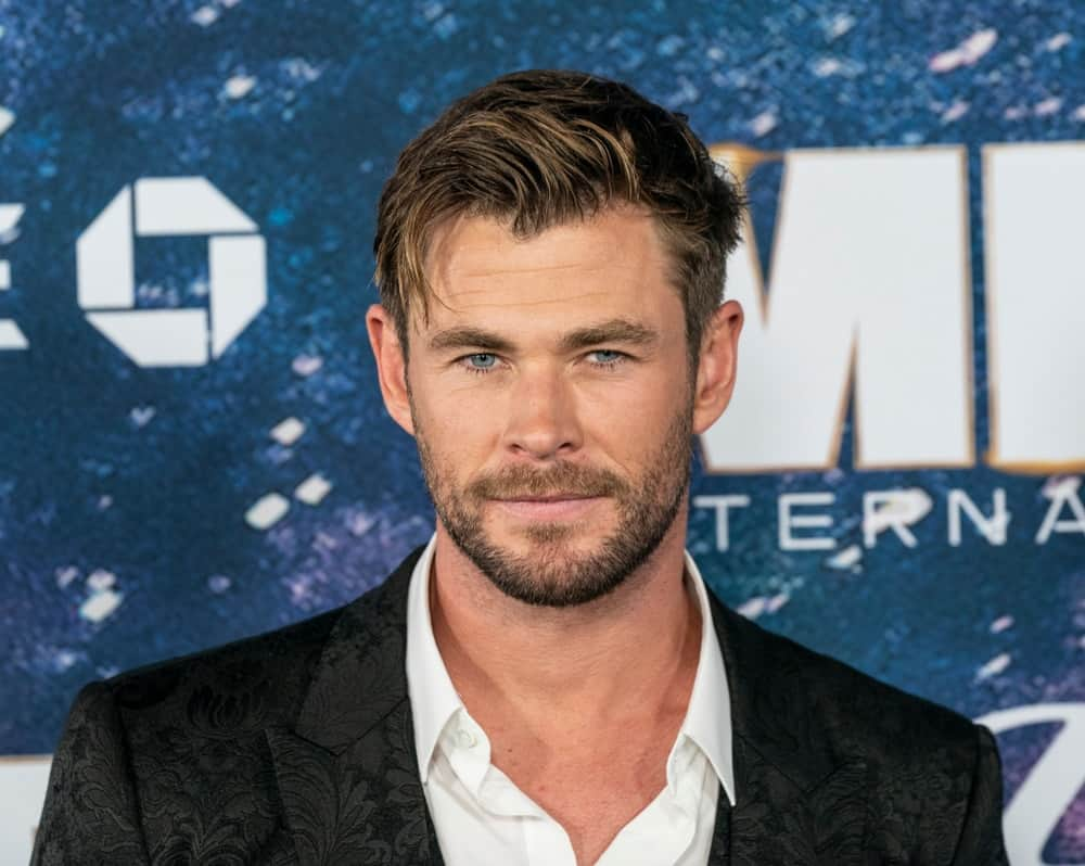 Last June 11, 2019, Chris Hemsworth wore a Dolce & Gabbana detailed black suit at the Men in Black: International premiere. He paired this with a highlighted tousled side-swept fade hairstyle capped off with a trimmed beard.