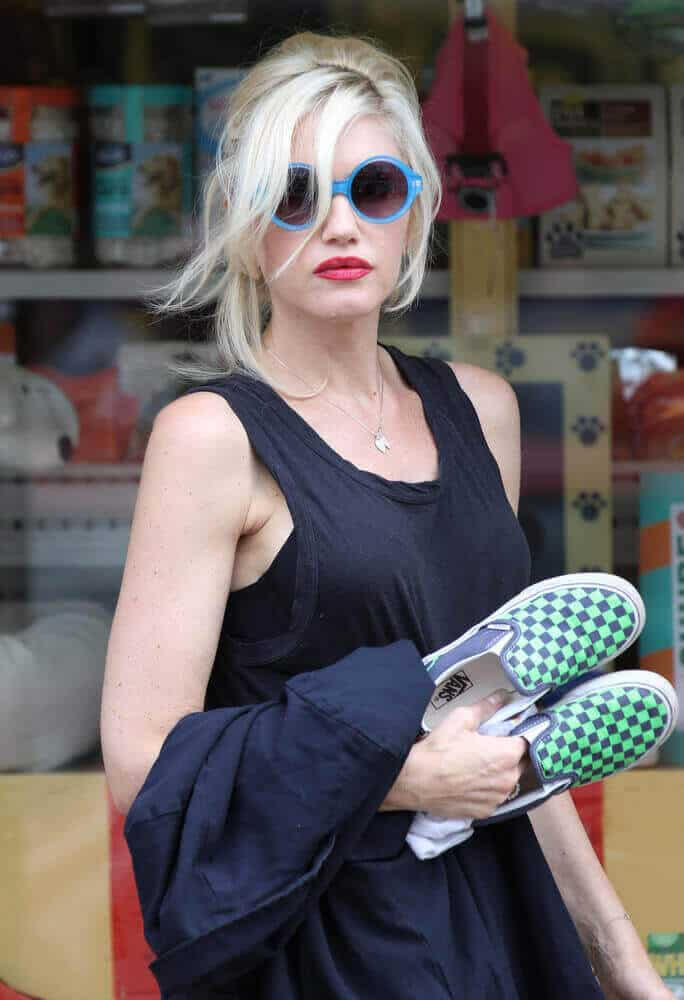 Gwen Stefani spotted in Primrose Hill, London on Aug 20, 2013 with a messy bun and long side bangs. She had her casual clothes on, together with her iconic blue sunglasses.
