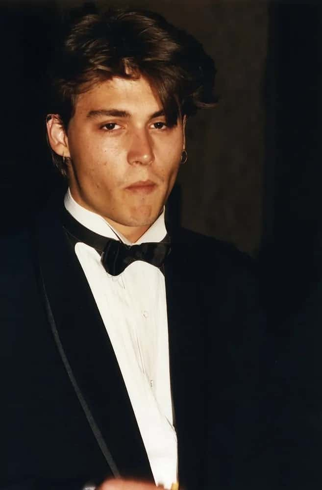 A young Johnny Depp steps out to a celebrity event held in Los Angeles, CA circa 1990 in the typical 90's boy-next-door look that is thick and center parted.