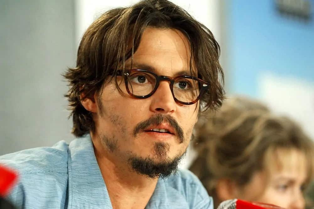 Johnny Depp appeared with a medium-length tousled hairstyle with a pair of glasses at the press conference for