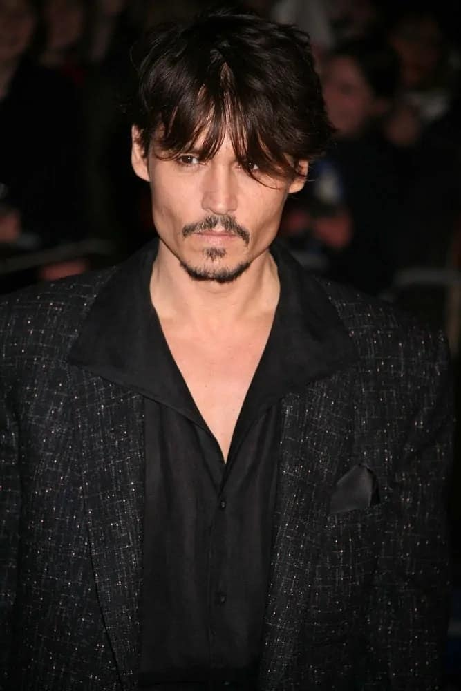 A leaner Johnny Depp looked brooding and gaunt under the veil of his dark wispy bangs when he arrived at the European Premiere of