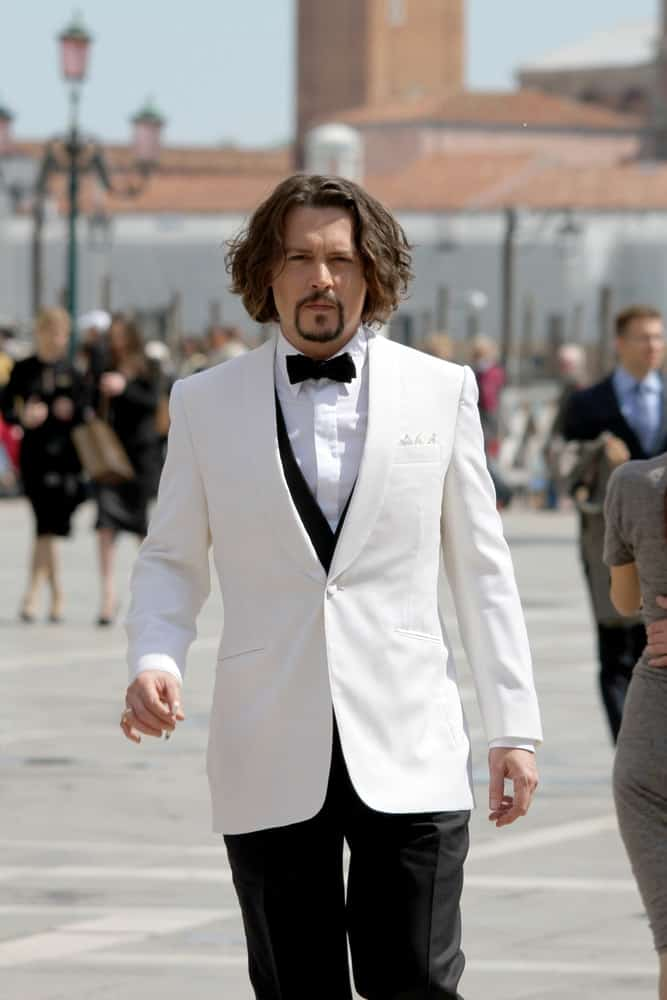 Actor Johnny Depp wore a slick white suit with his thick and long wavy hair with highlights during the film renewals of
