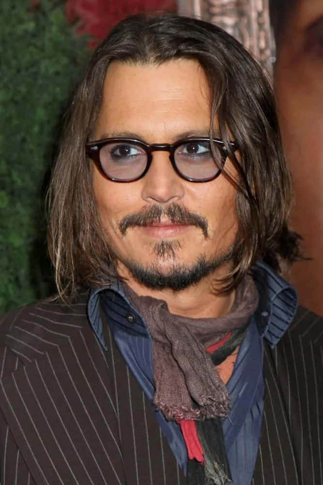Johnny Depp had his iconic and unique look with long wavy hair, colored sunglasses and some scarves during the New York premiere of