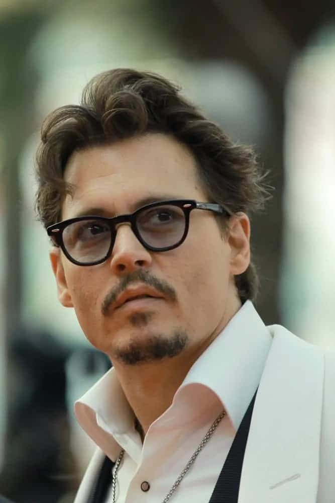 Johnny Depp looked classy with his brushed up tousled and wavy hairstyle and stylish mustache at the